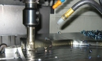 Chips fly as a CNC milling machine takes one of many passes across a prototype die.