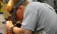 A journeyman Tool & Die Maker carefully removes the burrs from an aerospace part.