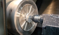 The 60HP main spindle spins a part with ease, making small dots of coolant look like streaks of white across the workpiece.