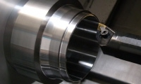 Chucked inside of a CNC turning machine, this part shines with a mirror-like surface finish.