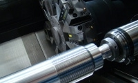 Stainless steel threads gleam in front of a tooling turret.