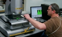 An operator prepares the CMM vision machine for the next cycle of parts to be inspected.
