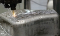 EDM drilling won't walk or move on angled surfaces, like on the curved face of this sheet metal stamping.