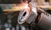 Sparks fly from a workpiece held in an angle fixture.