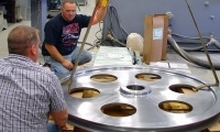 Two waterjet employees carefully prepare a large steel diameter for shipping.