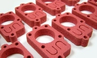 Precision waterjet cuts are possible through soft materials, like this red sponge-like material.