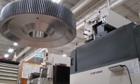 Large gear hangs from crane before wire EDM machining.