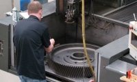 Tool & Die Maker clamps down an oversized gear inside a wire EDM machine.